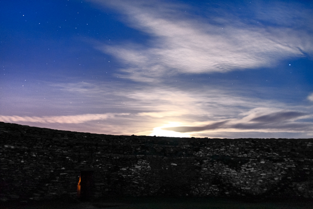 Moon coming up above the wall at 10.49 pm. The orange glow in the gate are from the lights of Derry.